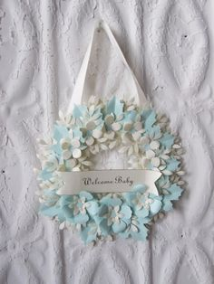 "Welcome Baby Wreath by carrieklein on Etsy. Small handmade paper wreath measuring about 6 inches with a banner saying ""Welcome Baby"". I began by cutting and forming the leaves and flowers from blue and cream papers and attaching them to the paper wreath. I have placed an ivory ribbon on the back so the wreath can be hung."