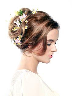 Wenn man einen Blick auf die Brautfrisuren 2015 wirft, sieht man vor allem eins: Blumen, Blumen und Blumen! Für diese Hochsteckfrisur zieht ihr einen Seitenscheitel, teilt eine Haarpartie vorne ab und toupiert die Haare am Hinterkopf leicht an. Jetzt fasst ihr die Haare zu einem lockeren Zopf zusammen, rollt Strähne für Strähne ein und steckt sie mit Haarnadeln fest. Anschließend noch ein paar Strähnen vorne mit dem Lockenstab eindrehen und frische Blumen ins Haar stecken.Von rockig bis…