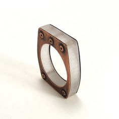 Title: Coherent  Oxidized copper adds depth and drama to this architectural ring. Bold thick resin forms the body to the curving lines of copper