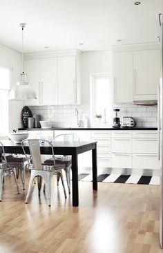 KITCHEN: White cabinets, long handles, black countertop, white tiling, wood floor