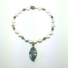 """Lucky Leaf is a 16"""" Coin Pearl, Sterling Silver and Green Swarovski Crystals with a Toggle Closure and an Abalone Shell Leaf Shaped Pendant. Product #6251"""
