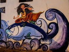 Eye catching street art from India. A beautiful girl astride a dolphin, looks to be the epitome of kindness and benevolence