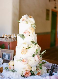 Scattered Juliet garden roses, light pink ranunculus, and green leaves will be scattered on top and on the tiers of the cake.