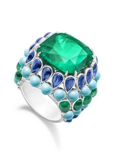 Ring in platinum set with 1 cushion-cut emerald 24 cabochon-cut turquoises 22 cabochon-cut blue sapphires and 10 cabochon-cut emeralds .