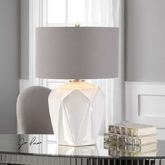 An embossed geometric pattern adds contemporary appeal to this glossy white ceramic table lamp from Uttermost. Shade is high x wide. Uses one maximum 150 watt bulb (not included). Style # at Lamps Plus. White Table Lamp, Light Table, Living Room Redo, Light Bulb Wattage, Lamp Shade Store, Transitional Wall Sconces, Ceramic Table Lamps, Cool Floor Lamps, Fashion Lighting