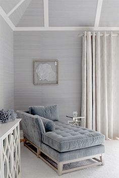 blye & gray gorgeous master bedroom design with blue gray velvet tufted settee fainting couch with blue velvet bolster pillow polished nickel accent table white lattice mirrored cabinet blue gray grasscloth wallpaper seafan art and ivory linen drapes.
