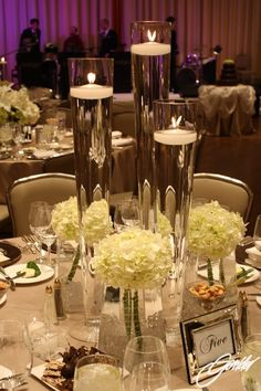 Tall vases with floating candles embellished with white hydrangea #wedding #reception #centerpieces