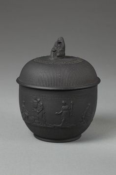 Sugar basin and cover (cover previously recorded missing), of black basalt with applied figures in low relief by E J Birch, depicting Peace, Liberty, Venus bound by cupids, and the Bourbonnais shepherd from a design by Lady Templetown. The dome-shaped cover and the lower part of the body are reeded.