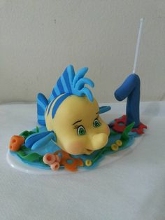 topo de bolo com vela linguado, peixinho mais fofo dos desenhos animados.