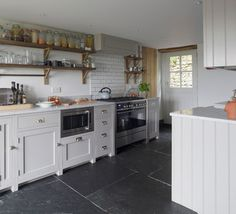 Update tradition This lovely kitchen in a Somerset cottage has many typical country ingredients, but the overall effect is anything but traditional. Open shelves, chunky units, a large range cooker and slate flooring here look fresh and considered, thanks to a few clever design touches. The slate flooring is supersized, for example, and makes a strong statement, while the metro tiles with dark grout as a splashback are a very now detail that would look just as good in an industrial kitchen.