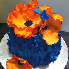 Blue fondant butterflies and orange abstract fondant flowers cake