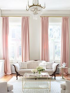 Tall soft pink curtains in this parlor. Greek key layered rugs and brass and glass cocktail table. velvet sofa. Interior design by SHOPHOUSE Kyle Born Photography www.shophousedesign.com