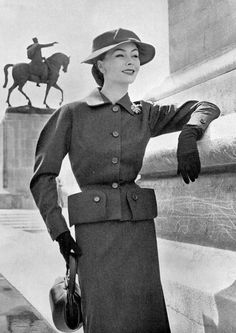 1952 gray wool suit, jacket has short folds on the side that form pockets, skirt is slightly flared for comfort, hat is of gray felt, by Jean Patou