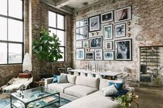 With massive ceilings and a brick wall, the gray couch paired with a colorful rug bring everything together.