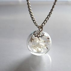Make a wish! Remember blowing a dandelion clock and making a wish when we were children? Those distant memories stay with us forever...This necklace has captured a piece of our sweet childhood memories. It features a large (20mm) glass orb with real dandelion seeds inside. This piece is absolutel...