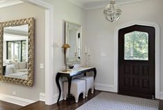 Design Ideas: Black And White Foyer With A Classic Side Table. glass vintage pendant light. classic console table. white tufted ottoman. brass finished table lamp. curved candle stick. framed wall mirror. dark door. geometric rug.