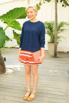 Michelle Williams wearing a Navy jumper over orange and white striped dress
