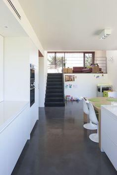 Donkere gepolierde beton in combinatie met een strakke, witte keuken.