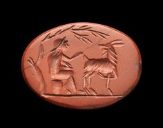 Gemstone made of red jaspis showing a satyr or paniscus seated on an upturned basket and caressing a goat turned to him, ground line. Roman, Augustan, 2nd half of 1st century B.C. Intact.