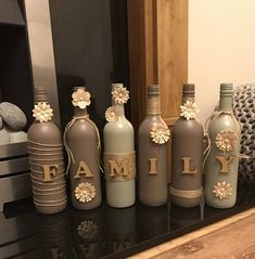 Spray painted wine bottles decorated with laser cut letters, twine and handmade paper flowers