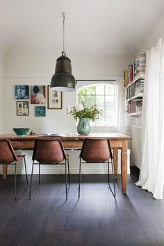 Leather modern chairs at a rustic wood dining table with a large metal industrial hanging light.