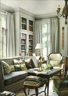 This is a long narrow space that incorporate shelving/design, a good sized sofa, Louis chair, coffee table.