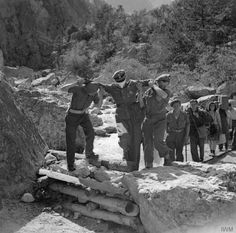 A blindfolded Waffen SS officer being led though the British lines at Tarviso in Italy to discuss terms of surrender. 7 May 1945.
