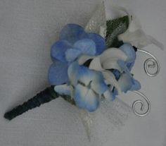 Sassy Sails Set sail this spring with Sassy Sails! White hyacinth buds sit nestled in waves of blue hydrangea, adorned with tulle, silver leaves, silver wire accents, and wrapped in wire along its stem. This prom season, plot your course and adjust your sails with Sassy Sails.  A designer's choice boutonniere, Sassy Sails uses hydrangea, hyacinth with tulle. Accessories include silver leaves, silver wire, and a wire stem wrap. Can be paired with the Sassy Sails corsage.