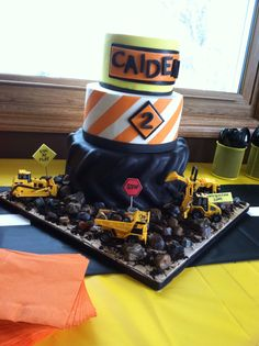 Construction party birthday cake. Bottom tier is a big tire, then stripes and a name plaque. Chocolate rocks complete the cake with mini construction trucks!