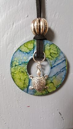 Washer pendant with alcohol ink. Finished off with a turtle charm, cording a bead.