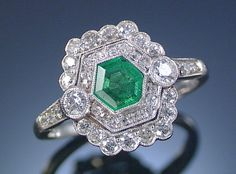 EMERALD AND DIAMOND RING, 1920S. Designed as a plaque, centring on a hexagonal emerald within similarly-shaped pierced surrounds millegrain-set with circular-cut diamonds
