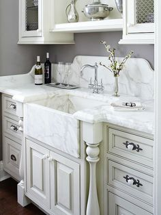 Furniture-style cabinet details and a marble backsplash and countertop enhance the sophisticated style of this wet bar. A small-scale apron-front sink provides plenty of space for soaking glasses, while mesh-wire panels add interest to cabinet doors. Cozinha Shabby Chic, Shabby Chic Kitchen, Shabby Chic Homes, Kitchen Decor, Kitchen Display, Kitchen Sinks, Kitchen Ideas, Kitchen Cabinets, Beautiful Bathrooms