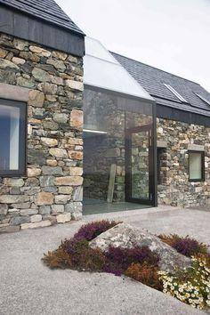 Bruchsteinzeug mit großformatigen Fensterfronten gelungen verbunden