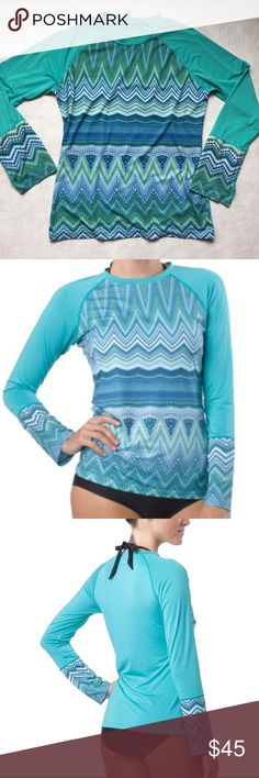 PrAna Rory Rashguard in Lagoon - sun protective Long sleeve crew neck rashguard shelters you from the  sun with UPF 50+ while surfing, paddleboarding, or enjoying any water activity. 91% polyester 9% spandex. Quick drying and stretchy. Standard fit not too tight and not too loose. Bust 39-40, sleeve length 32.5, waist 31-32, equivalent to size 12-14 (measurements from the REI website). Beautiful ocean blue color with geometric wave design. Excellent condition! Prana Tops