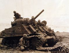 80-G-304853: Battle for Iwo Jima, February-March 1945. This General Sherman tank on Iwo Jima was wrecked by a land mine and hit five times by Japanese artillery fire, but is Fourth Marine Division crew escaped without casualty. In turret, Sergeant James W. Reeses. Under the gun, left to right: Corporal Lynn S. Evans and Private First Class Lloyd F. Spickate. Charles H. Saulman is examining the damaged tread. Photographed released, February 26 1945. U.S. Navy Photograph.