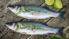 Two raw seabass with lime and rosemary by nblxer. Two raw seabass with lime and rosemary on the wooden background Creative Infographic, Photoshop, Sea Bass, Wooden Background, Fish And Seafood, Cherry Tomatoes, Clean House, Lime, Herbs