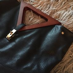 """Black vegan leather handbag Unique faux leather bag, that looks and feels like real black leather.  Has dark wood triangular handles, gold hardware and hooks for a strap (strap not included).  This can also be carried as a clutch.  Inside is very clean, outside has a few scuffs.  12.5"""" X 16"""". Bags"""