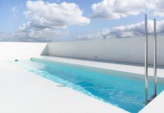 Un primo piano della piscina sull'ultimo piano della casa Pool K. Linee essenziali e tonalità total white
