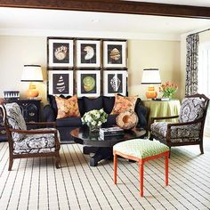 Keeping Busy - A stunning arrangement of graphic artwork showcased over the sofa, plus punches of lively orange and green, connect multiple patterns and solids into an energetic living room setting.