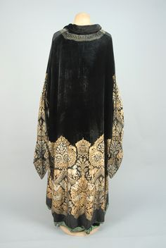 "MARIA GALLENGA STENCILED VELVET COAT, 1920s  Black silk stenciled in a metallic silver and gold Medieval pattern having dogs, birds and griffins, narrow pointed sleeves, self tie at neck with metallic gold and silk tassels, green silk faille lining having stenciled border signed ""Maria Monaci Gallenga"". B-52, L-52."