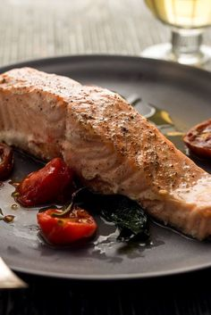 """NYT Cooking: Here is a dead-simple recipe for salmon prepared en papillote (a fancy name for """"in paper,"""" though like most everyone else these days, you will use aluminum foil). Layer salmon, tomato and basil on lightly oiled foil and wrap it all up — you can even do it a night before cooking. When the time for dinner comes, you can steam, grill, roast or pan-grill the package..."""