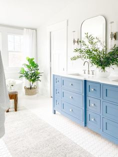 Primary bathroom design featuring classic and contemporary elements. The custom blue vanity including a linen closet is balanced by white quartz countertops, light gray walls, and white tile. #SherwinWilliamsReservedWhite #BenjaminMooreLazySunday #BlueBathroomVanity #PaintColor #LightGrayBathroomWallsWithBlueVanity #dbCPHistoricEdgefieldProject Blue Bathroom Vanity, Blue Vanity, Light Grey Walls, Gray Walls, Classic Bathroom, Loft Style, White Tiles, Quartz Countertops, Bathroom Interior Design