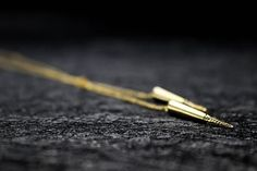 Long modern lariat necklace for women with gold spikes.