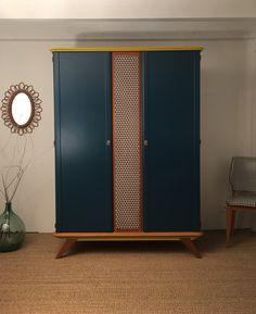 L'armoire vintage Léontine a été entièrement restaurée. Ses couleurs : Bleu canard, moutarde, orange et tissu imprimés géométriques bleu, orange, moutarde.
