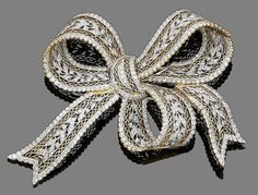 A diamond bow brooch Designed as a bow decorated with a garland of leaves, set throughout with brilliant-cut diamonds, diamonds approx. 3.75cts total, length 9.0cm