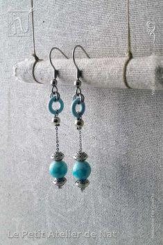 Réalisation [ Fait-Main ] avec du fil aluminium (Ø2mm), une perle de verre peinte et des perles tibétaines, ainsi qu'une perle d'acier inox et un anneau d'aluminium laqué. Les crochets d'oreilles sont en acier inoxydable ainsi que la chaîne. Petites boucles d'oreilles ou boucles d'oreille à assortir avec tenue et maquillage, selon l'envie. Facile à mettre et enlever, la boucle d'oreille est légère et se dandine au gré des mouvements, avec de petits tintements agréables qui permettent de...