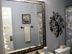 How to frame a bathroom mirror already mounted on the wall. This is so pretty. I think I'll try it.