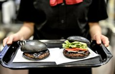 A Burger King employee holds two black hamburgers at a company restaurant on September 18, 2014 in Tokyo, Japan. The black burgers, one a Kuro Pearl (L) at 480 yen, has black buns and cheese smoked with bamboo charcoal and black sauce made of squid ink. The other, the Kuro Diamond at 690 yen, comes also with lettuce, tomato, onion and mayonnaise. The burgers are available from September 19 through early November in Burger King restaurants throughout Japan. (Photo by Keith Tsuji/Getty Images)