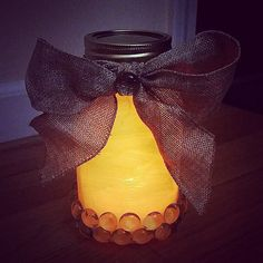 Pin for Later: The Ultimate Guide to Decorating With Mason Jars This Halloween An Orange Lantern Pop an LED light inside a jar painted orange, and add accent with a black bow.