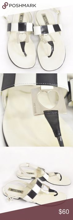 """Moschino White & Black Cutout Heart Thong Sandals Fabulous authentic hard to find Moschino black & white leather thong sandals with silver-tone metal cutout heart detail engraved with """"Moschino"""". Low block heel. Made in Italy.  Size: 39 or 9 Heel Height: 3/8""""  Condition: Light yellowing/discoloring & a few small dots on the footbed, couple very light scratches on the metal detail, couple glue marks, light wear at the tips of the toes, tiny mark on the back of the left heel and normal wear to…"""